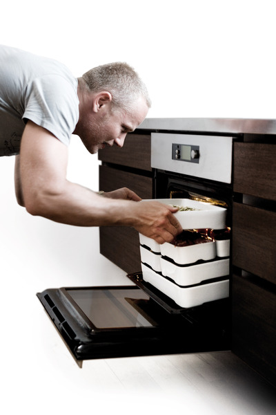 Man_putting_stackable_oven-to-table_cookware_by_christian_bjorn_into_oven-sixhundred
